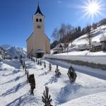 Tief verschneit zeigt sich der Friedhof rund um die Hüttschlager Kirche