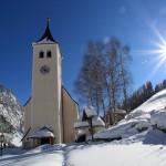 Die Pfarrkirche von Hüttschlag, geweiht dem hl. Josef, links im Bild ein riesiger Eisfall