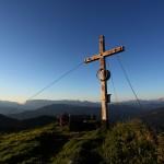 """Die warme Abendsonne beleuchtet das Kreuz auf der """"Gabel"""" (Kitzstein, 2.037 m), hinten v.l.n.r.: Hagengebirge, Tennengebirge, Bischofsmütze, Dachstein"""
