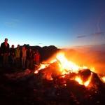 Wanderer kommen vom Tal herauf und halten Rast am Sonnwendfeuer