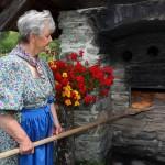 Marianne holt das fertige Brot aus dem Steinofen